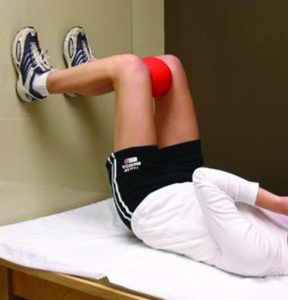 Patient doing ball squeeze exercise with feet against the wall