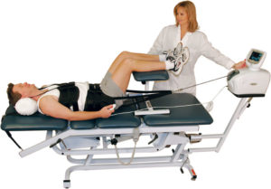 man receiving lumbar traction from a physical therapist