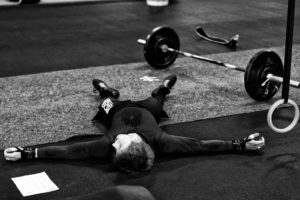 picture of a gymnast exhausted after lifting weights