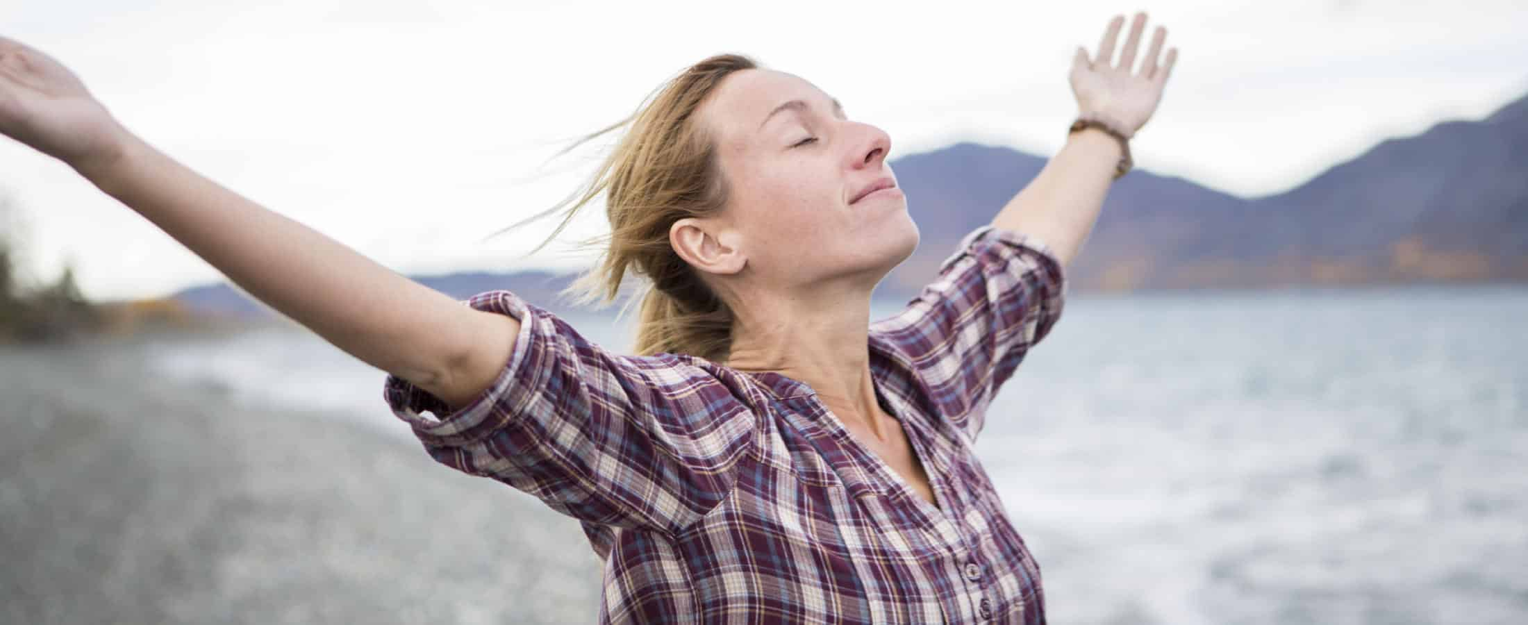 woman relaxing with her arms wide open and water and mountains in the background