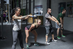 picture of multiple people doing kettle bell lifts