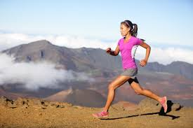 a woman running with mountains in the background